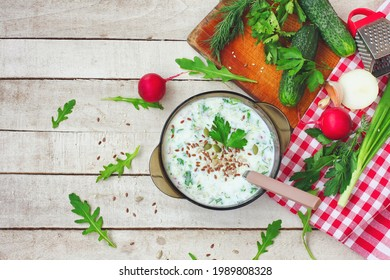 sopa veraniega de fir frío en tazón de vidrio con hierbas picantes, pepino, rábano sobre mesa blanca de madera, comida vegetariana