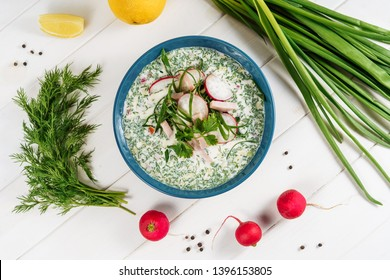 Summer Cold Yogurt Soup Okroshka Bowl Flat Lay. Russian Radish and Cucumber Vegetable Tarator Decorated with Green Onion and Dill Top View for Recipe Ingredient. Restaurant Food on Wooden Table