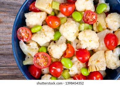 summer colorful cauliflower salad bowl with edamame and cherry tomatoes over a wood table