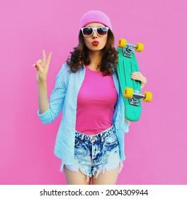 Sommerfarbiges Portrait von stylischen jungen Frauen-Models, das mit grünem Skateboard steht und ihre Lippen mit rosafarbenem Hut auf dem Hintergrund weht