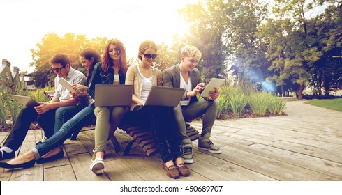 summer, communication, technology , education and teenage concept - group of students or teenagers with laptop and tablet pc computers at park or campus