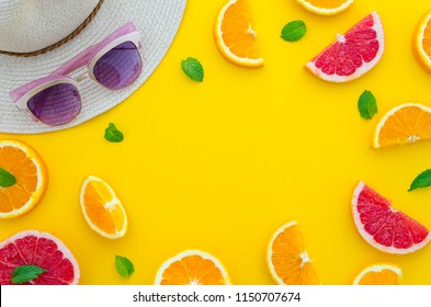 Summer composition arranged in a frame of sliced citrus fruits with little mint leafs, a summer hat and sun glasses on bright yellow vibrant flat lay background. Use it for your hand lettering mockup