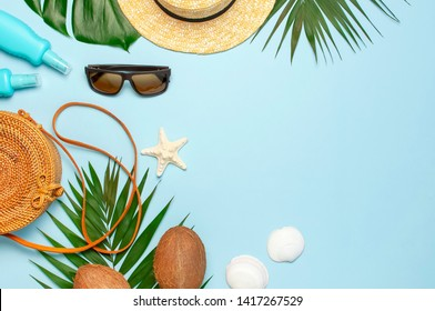 Summer composition flat lay. Round trendy rattan bag straw hat sunglasses tropical palm leaves coconut sunscreen seashells on blue background. Top view copy space. Creative fashion vacation backdrop