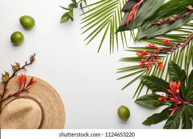 Summer composition. Fruits, hat, tropical palm leaves and flowers on white background. Flat lay, top view, copy space.