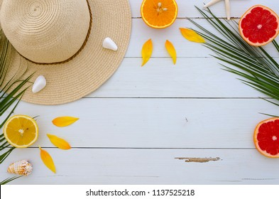 Summer composition. Fruits, hat, tropical palm leaves, seastones on pastel yellow white wooden background. Summer concept. Flat lay, top view, copy space
