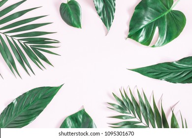 Summer composition. Green tropical palm leaves on pastel pink background. Summer concept. Flat lay, top view, copy space