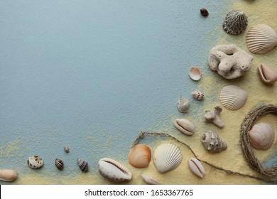 Summer composition in a minimalist style with shells and sand on a blue background. Imitation of the beach and sea, flat lay.