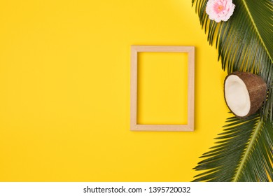 Summer composition with photo frame, green palm leaves, and cocunut on a yellow background. Artwork mockup with copy space