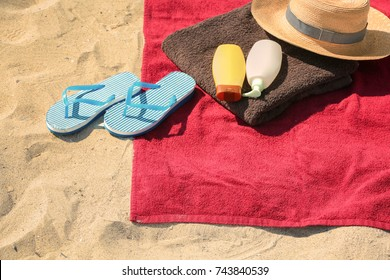 Summer composition with red beach towel on sand