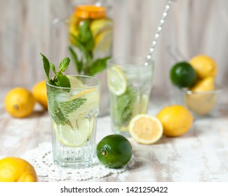 Summer composition with refreshing healthy alcohol free home made lemonade with pepper mint, limes and lemons. White lace napkin as decor, wooden background. Vacation mood, enjoying summertime