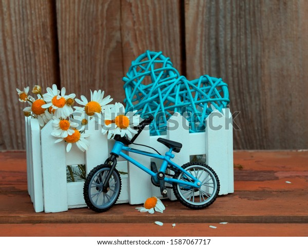 A summer composition with a small bicycle, a white box in the form of a fence, with a heart and chamomile flowers, on an old worn wooden background. Daytime romantic scene.