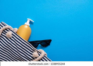Summer composition. Stripped beach bag with suntan cream and sunglasses. Summer holiday concept, sunscreen cosmetic and accessories on blue sea background.