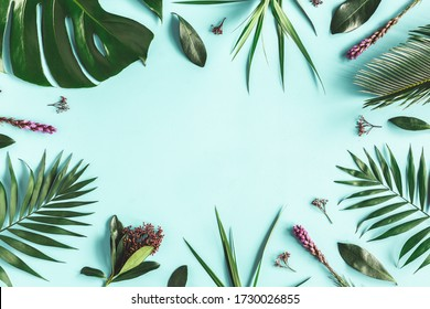 Summer composition. Tropical flowers and leaves on blue background. Summer concept. Flat lay, top view, copy space