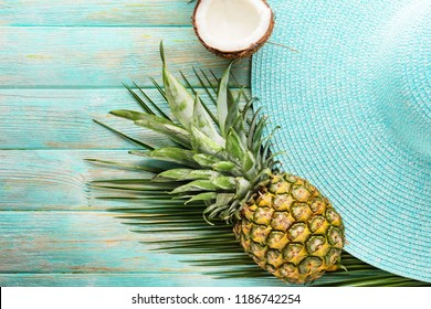 Summer composition with tropical fruits and beach hat on wooden background