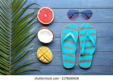 Summer composition with tropical leaf, fresh fruits and beach accessories on color wooden  background