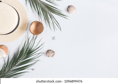 Summer composition. Tropical palm leaves, hat, coconut on pastel blue background. Summer concept. Flat lay, top view, copy space