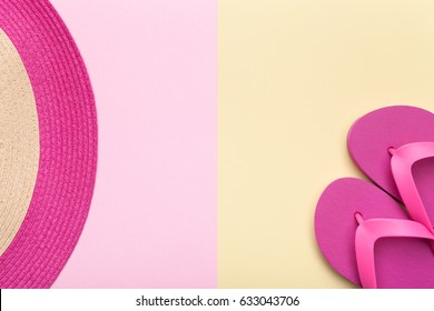 Summer concept. Beach hat and flip flops on pink and yellow background. Flat lay. Minimal style. Copy space. Top view.