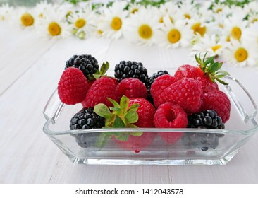 Summer concept, summer berries, strawberries, raspberries, blackberries in glass tray and white daisies on a white painted wooden table