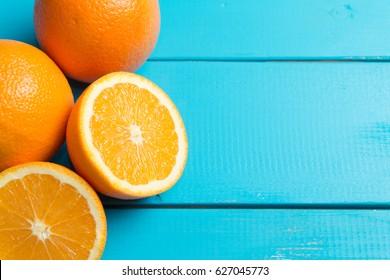 Summer concept : Cutted orange lying on colorful wood table.