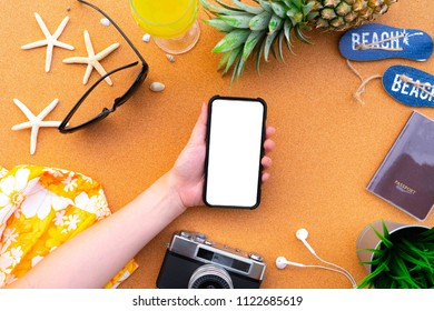 Summer Concept , Flat lay hand use smartphone on tropical fruit pineapple , camera and travel accessories on sand background include copyspace for add text or graphic