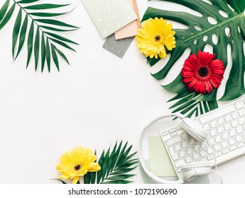 Summer concept, flat lay tropical leaves with headphones, keyboard, and flowers.