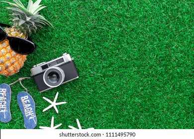 Summer Concept , Flat lay tropical fruit pineapple , camera and travel accessories on grass background include copyspace for add text or graphic
