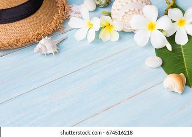 Summer concept with hat, seashell and flowers on blue rustic wooden background with space