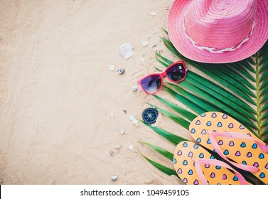 Summer concept with hat,sunglasses,sandals and compass on sand beach.
