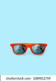 Summer concept image: orange sunglasses with palm tree reflections isolated in pastel blue background. Symbolic for hot summer, sun protection, hot days and tropical travel vacation. Vertical frame.