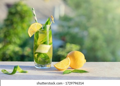 Summer concept. Lemonade or mojito cocktail with lemon, cucumber and mint, cool refreshing drink or beverage, outdoor.  Cold detox water with ice  and paper straw, copy space. - Shutterstock ID 1729796314