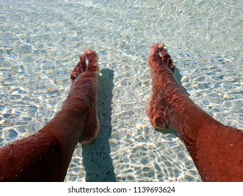 Summer concept, mans feet in a paddling pool