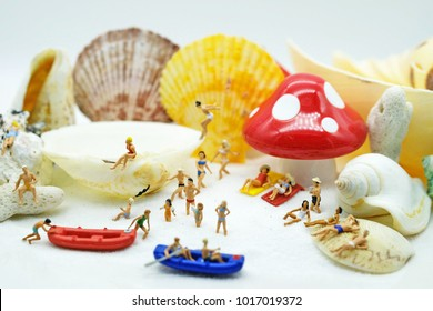 Summer concept : Minature people enjoy on the beach with the beautiful white sand.some on the boat some cheering and playing on the beach.