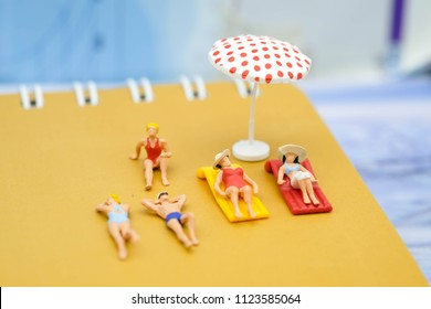 Summer concept : Minature people are taking sun bath on the beach notebook with the colorful umbrella use as travel background and holidays.