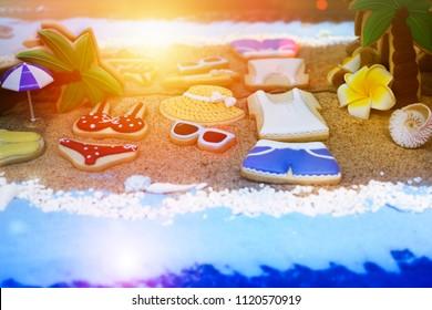 Summer concept of sandy beach, bikini, straw hat, shells and  sunset