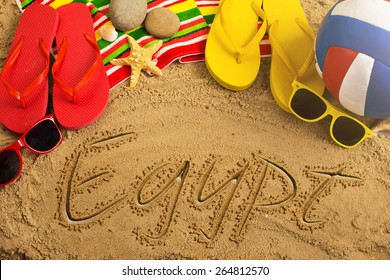 Summer concept of sandy beach, colorful thongs shoes, sunglasses, ball and inscription
