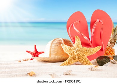 Summer concept of sandy beach, straw hat, shells and starfish.