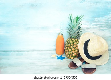 Summer concept stillife - ripe pineapple, straw hat, flip-flops and a bottle of multivitamin juice in front of a blue rustic wooden background.