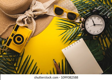 summer concept with travel stuff camera notebook glasses and woman hat flatlay image on color background with free copy space