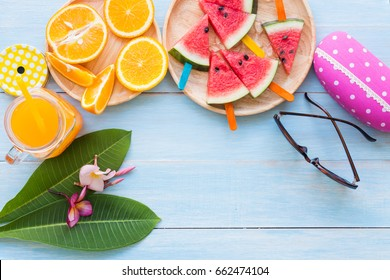 Summer concept with tropical fruits orange and watermelon slices on blue rustic wooden table background