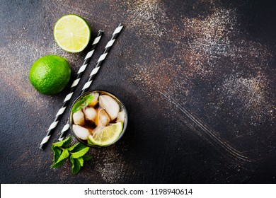 Summer cooling alcoholic beverage from cola, whiskey, lime and liqueur in glass on dark concrete old background. Top view.