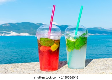 Summer cooling drinks. Two mojitos on the beach. Close up. Red and green cocktails on blue sea background. Refreshments