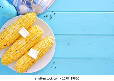 Summer corn on the cob. Top view scene, side orientation on a blue wood background.