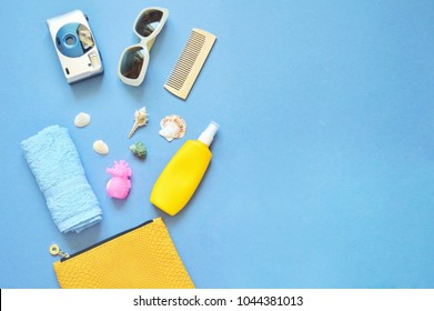 Summer cosmetic bag content. Blue terry towel, camera, sunglasses, wooden comb, toy sea horse and seashells. Flat lay photo, travel concept. Free space for text, mock-up