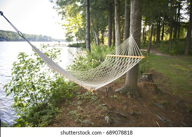 Summer cottage life with hanging hammock facing lake