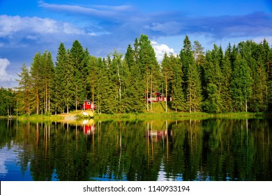 Summer cottage or log cabin by the blue lake in rural Finland. Idyllic countryside landscape view with blue water and green forest.