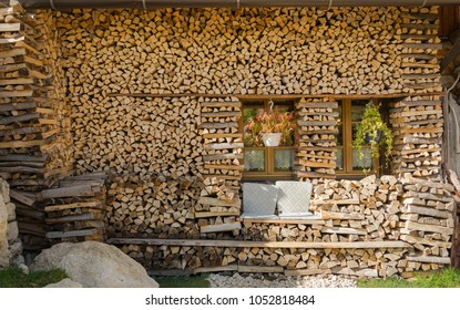 Summer cottage in village in Alps with big pile wood, grey stone, two windows and handmade seats for relax