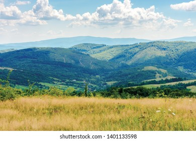 summer countryside in mountains. rural field on the hill. village in the valley. ridge in the distance. cloudy weather