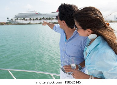 Summer couple on the boat pointing at a cruise