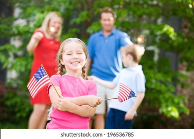 Summer: Cute Girl Holding American Flags With Family Behind