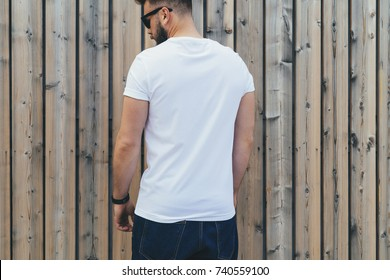 Summer day. Back view. Young bearded hipster man dressed in white t-shirt and sunglasses is stands outdoor against wood wall. Mock up. Space for logo, text, image.